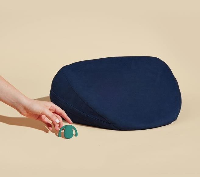 The tiny egg-shaped vibrator with two handles and wedge pillow