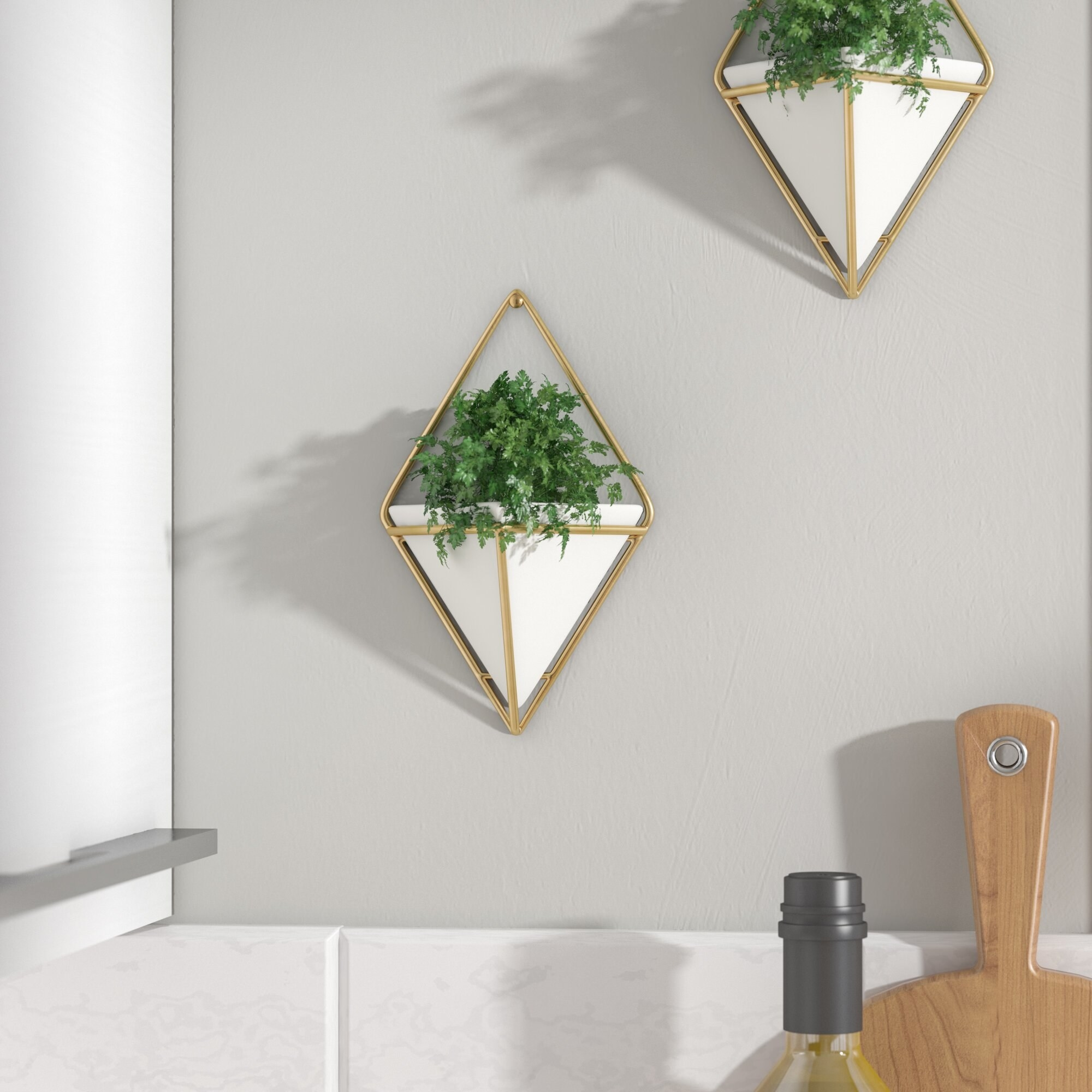 Two white triangular planters hung by gold diamond-shaped frames
