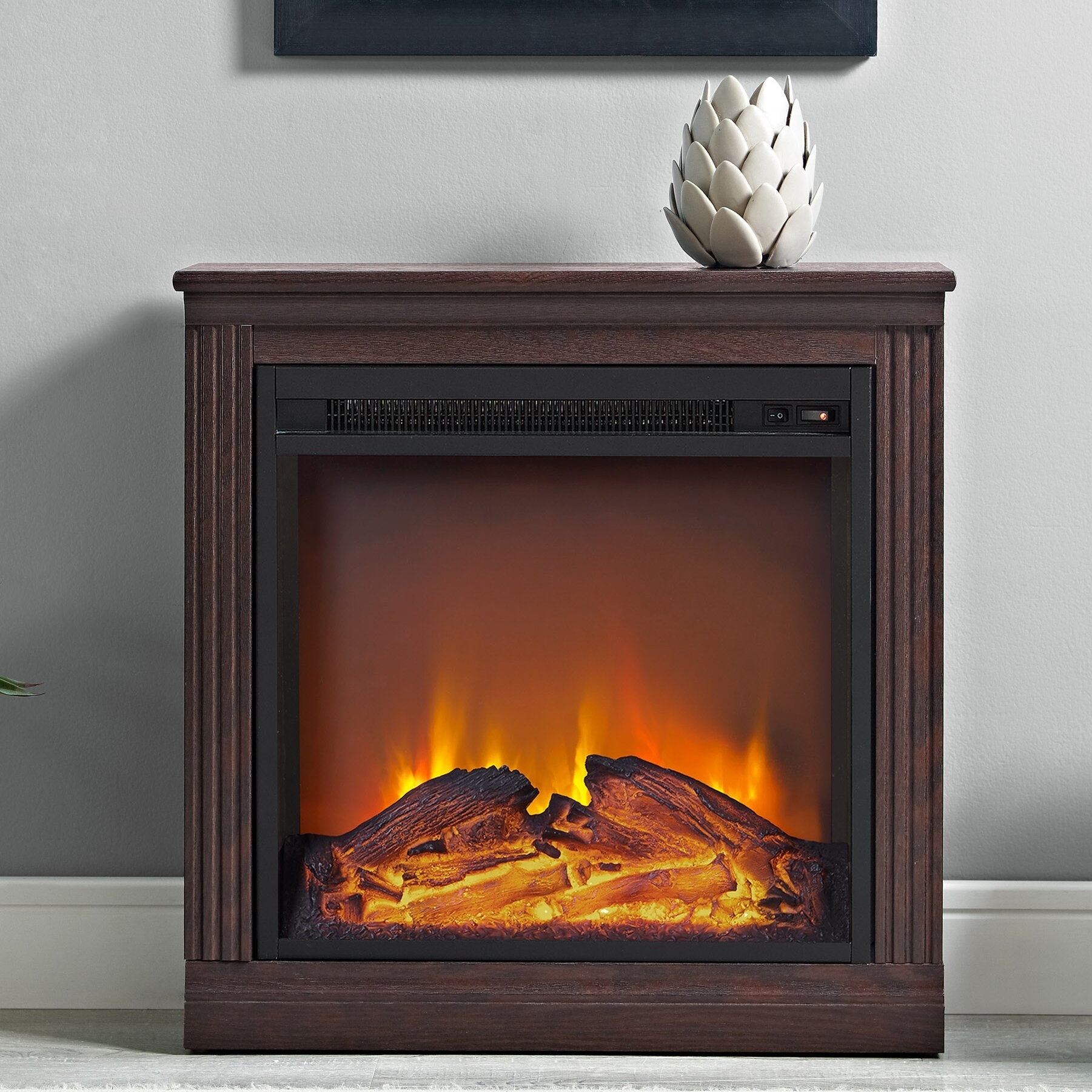 A small electric fireplace with fake wood on fire in it and wood paneling on the sides in a living room