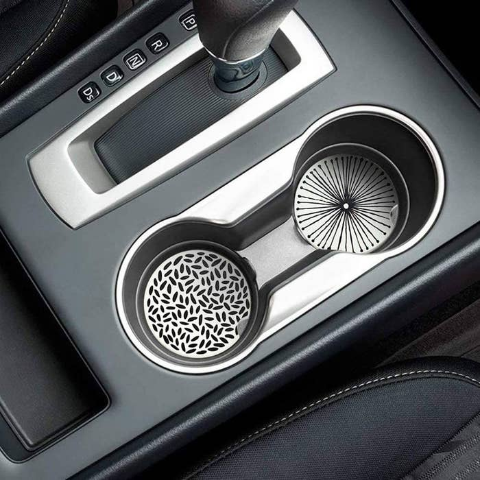 Two patterned coasters inside of a car cupholder
