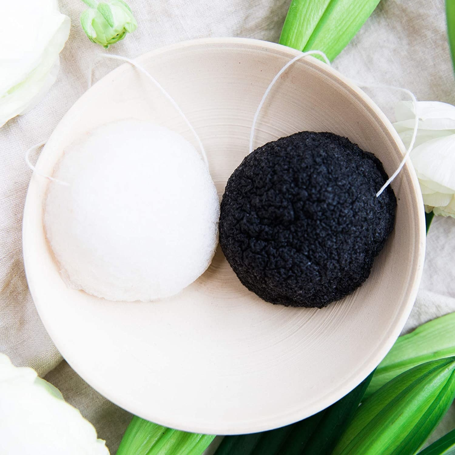 Two konjac sponges in a ceramic bowl