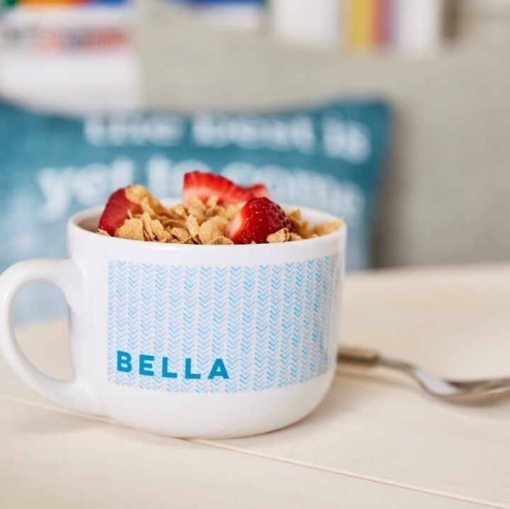 """Large mug with cereal in it that says """"Bella"""""""