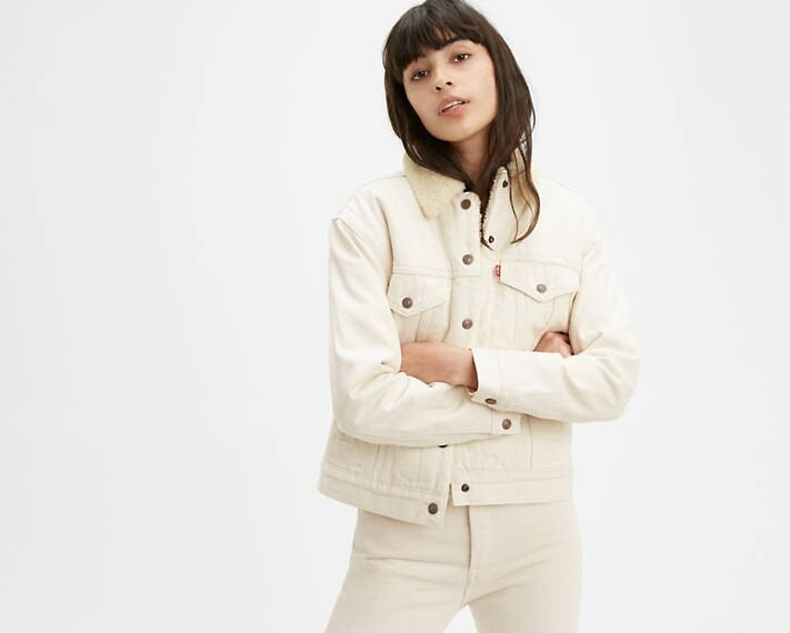 Model wearing the white jacket with a sherpa collar