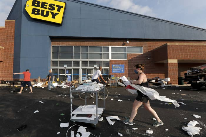 People clean up scattered debris and trash in a parking lot outside of a Best Buy store.