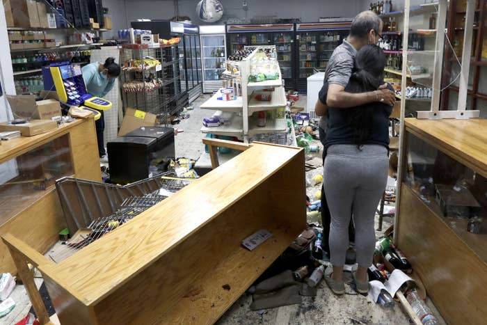 A man hugs his adult daughter amid their vandalized store, where the floors are scattered with bottles and a table is overturned