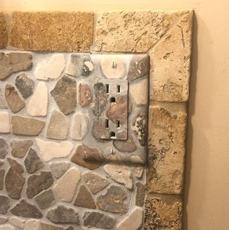 A wall outlet painted with rock designs that match the pattern on the wall