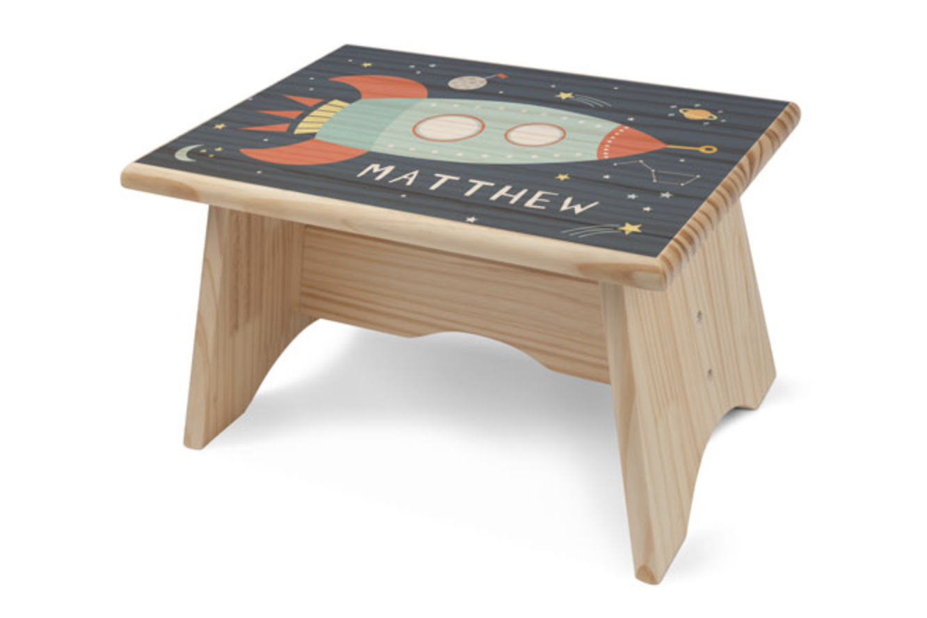"""A wooden step stool with a space ship print and """"Matthew"""" spelled out below"""