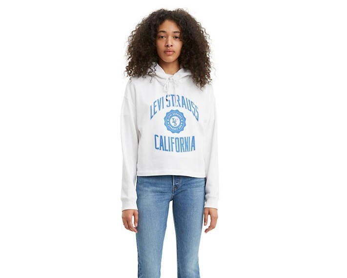 Model wearing the hoodie in white that says Levi Strauss California in blue letters