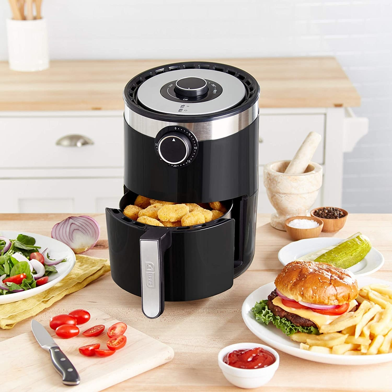 The cylindrical air fryer in black, featuring an analog timer, temperature dial, and handle on the cooking basket