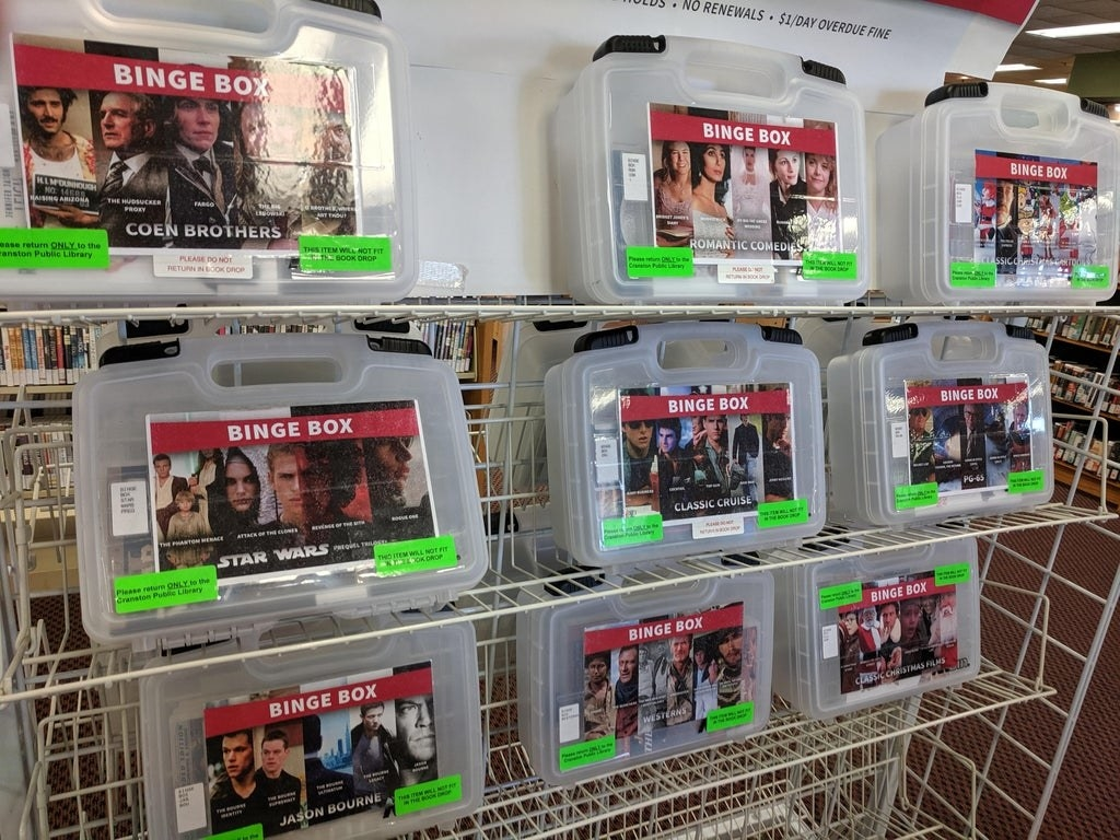 Plastic boxes holding several movies of the same genre