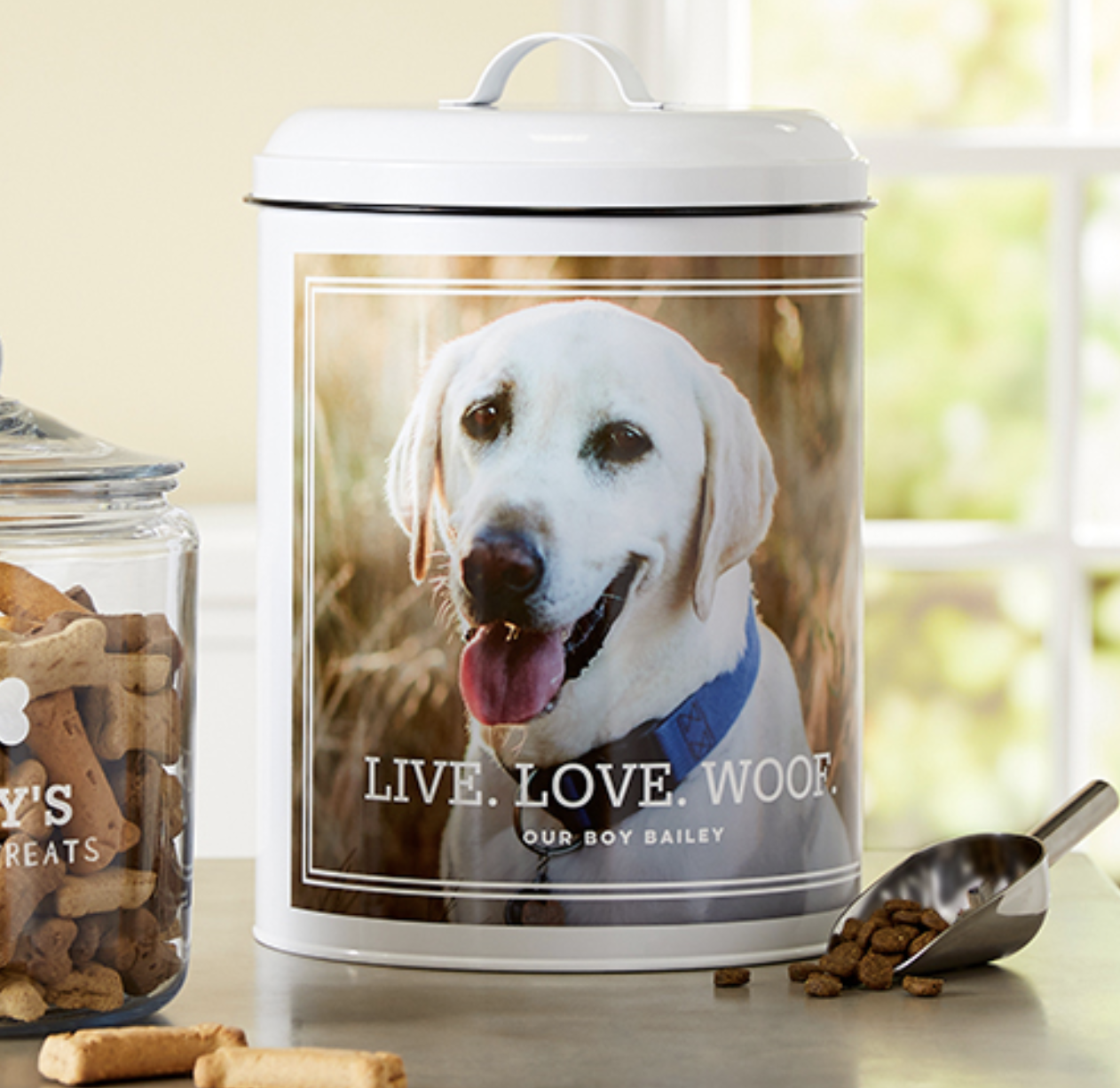 """A treat jar with a photo of a dog and print that says, """"Live. Love. Woof. Our boy Bailey"""""""