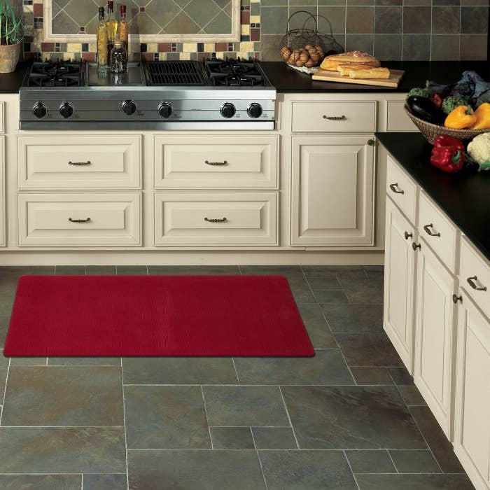 Red anti-fatigue kitchen mat placed on dark gray tiles in a kitchen with white cabinets