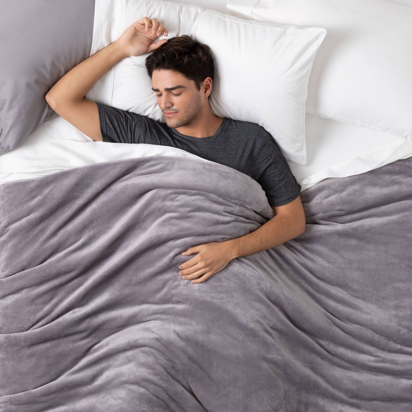 Model wears dark gray microplush weighted blanket in a bed with white sheets and pillows