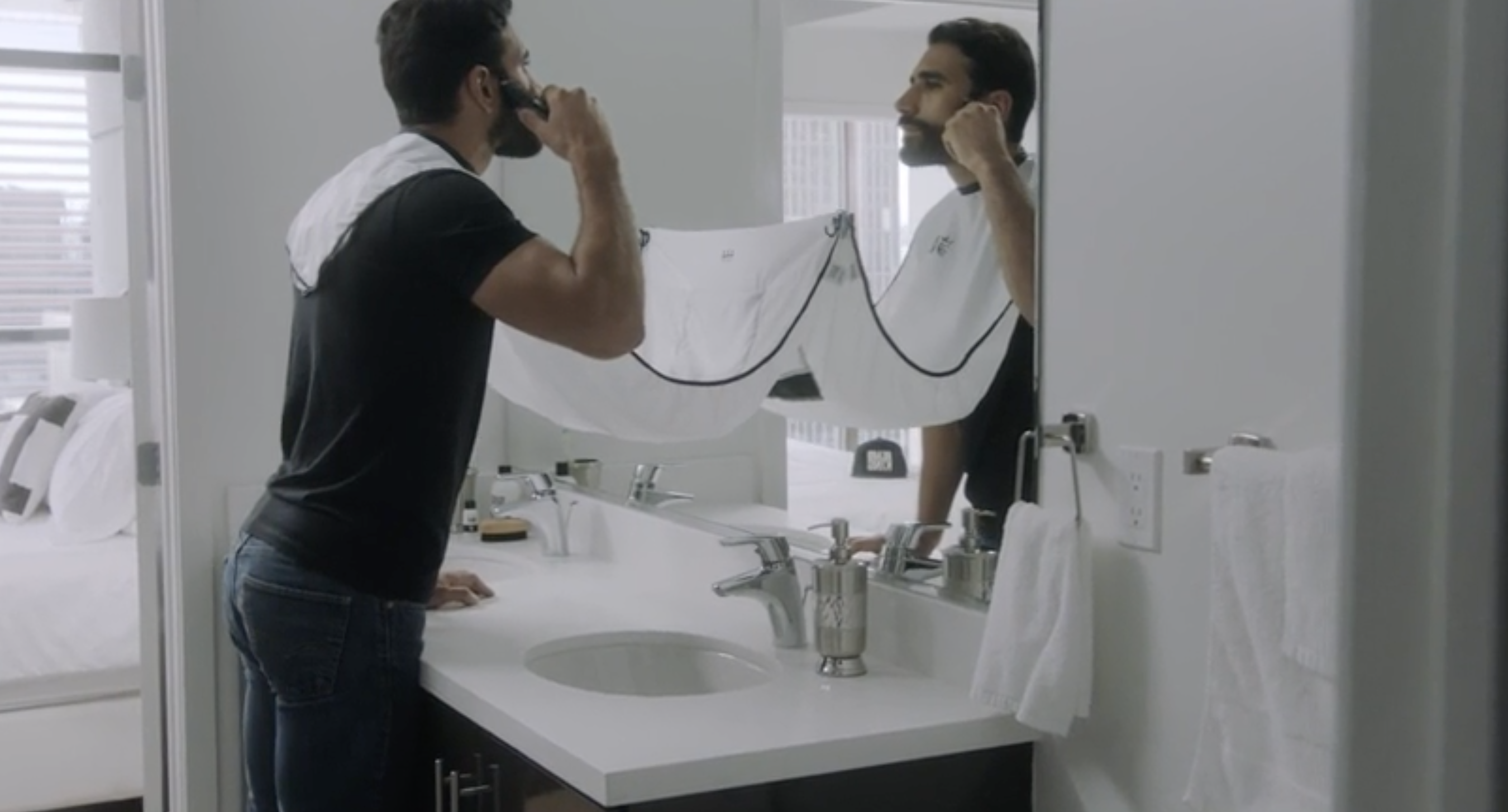 "A model trimming their beard over a plastic ""bib"" that is attached to their neck and suctioned to the bathroom mirror"