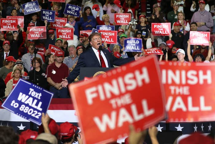 """Photo of a Trump rally with people holding signs that say """"FINISH THE WALL"""""""