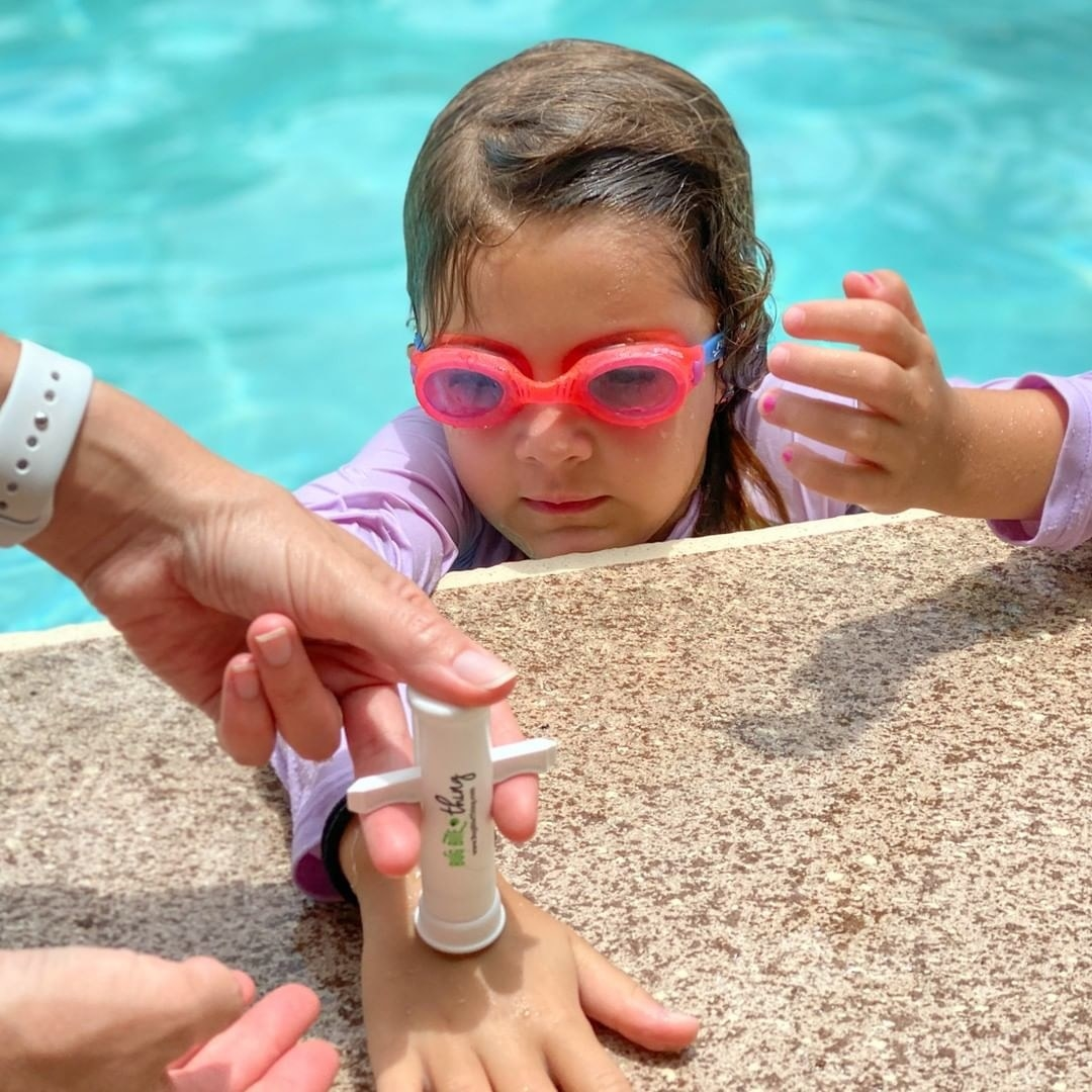 A person uses the suction tool on a child's hand as they hang on the side of a pool
