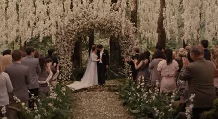 Bella and Edward beneath a floral arch