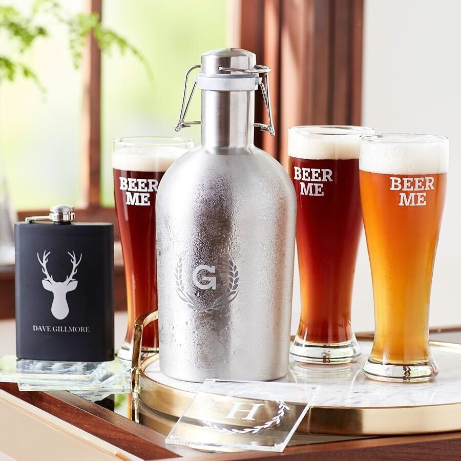A table full of custom barware, including a flask, growler and beer glasses