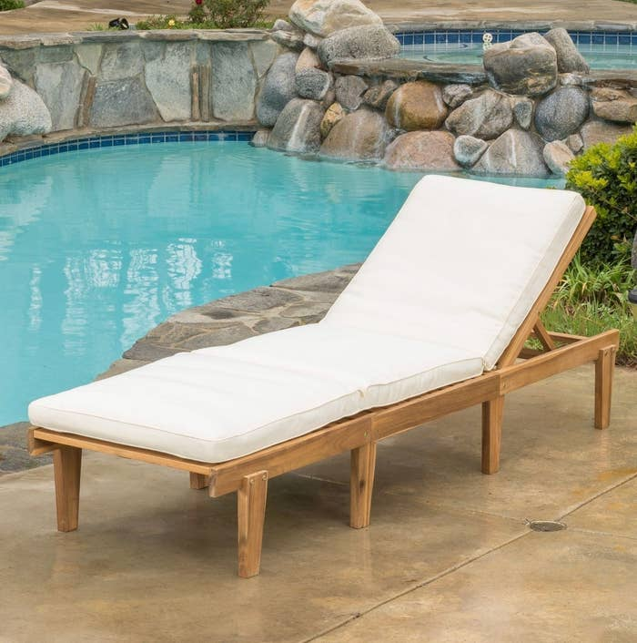 White outdoor chaise lounge with wood legs placed next to a pool ledge outdoors
