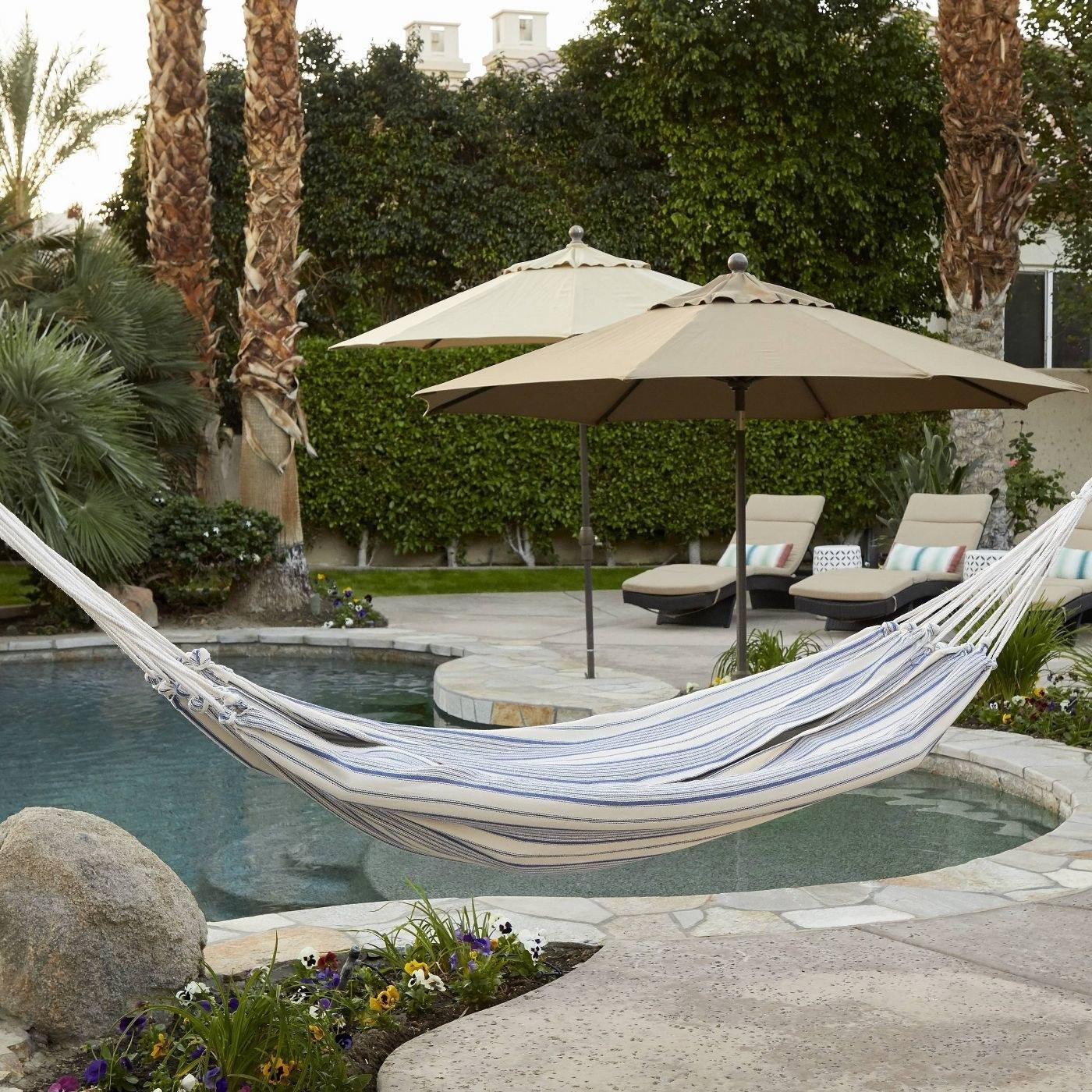 Striped flat-weave hammock above a circular pool in a backyard