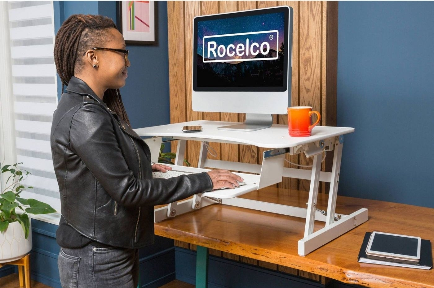 Model works with monitor perched on white standing desk above a wooden desk