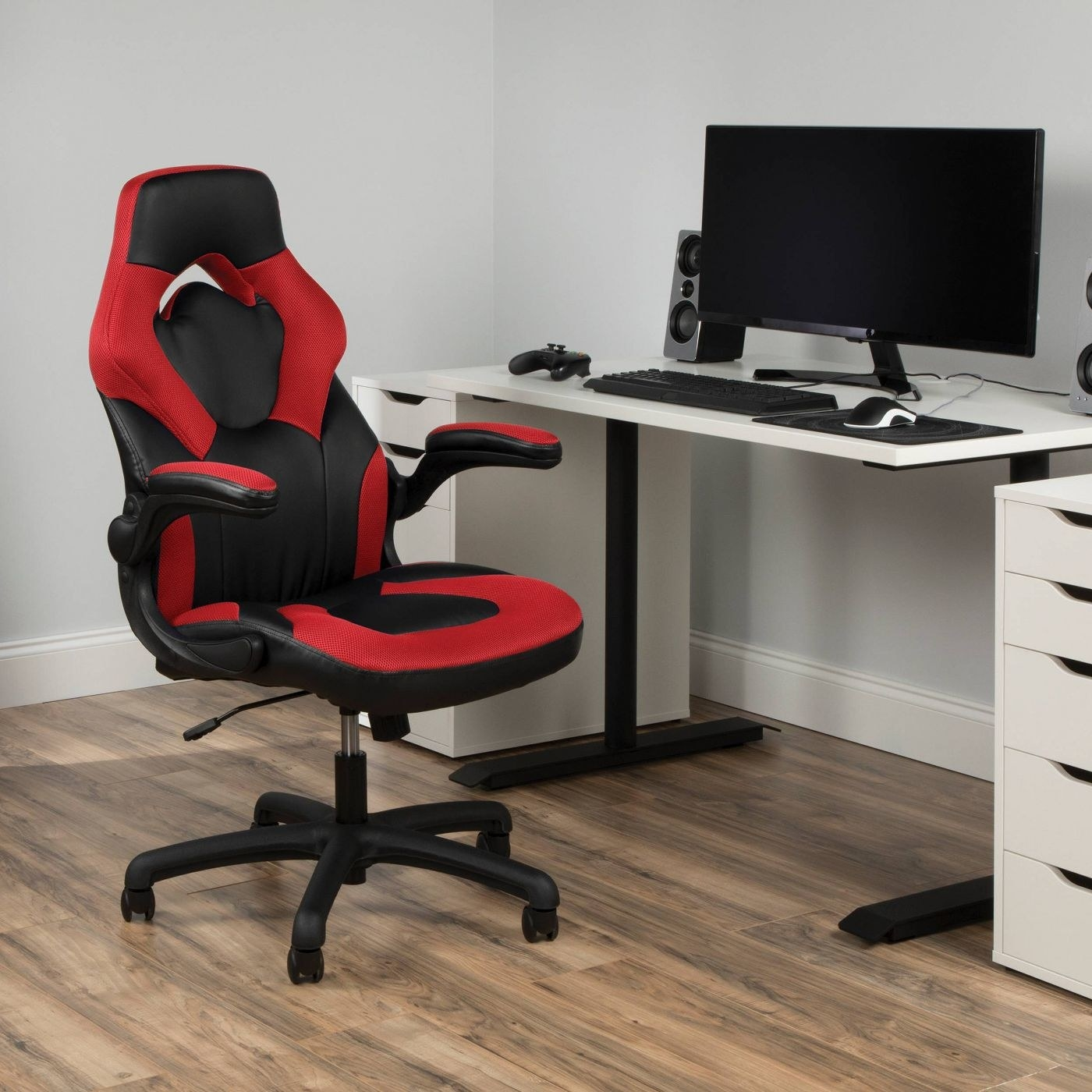 Red gaming chair next to white desk with black computer monitor, keyboard, and gaming console