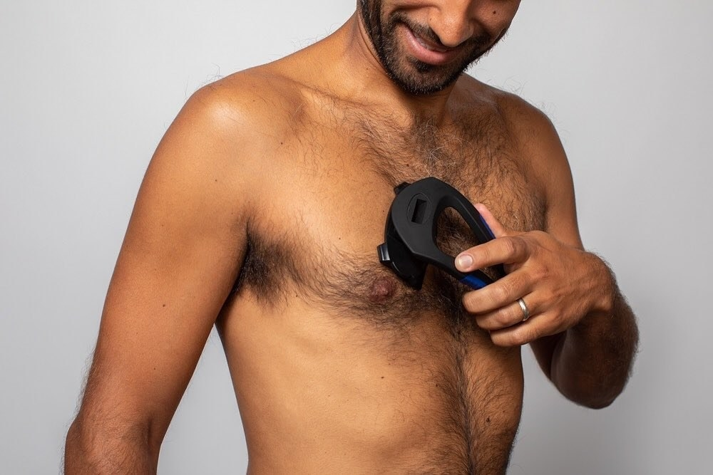A smiling person using the shaver to trim their chest hair