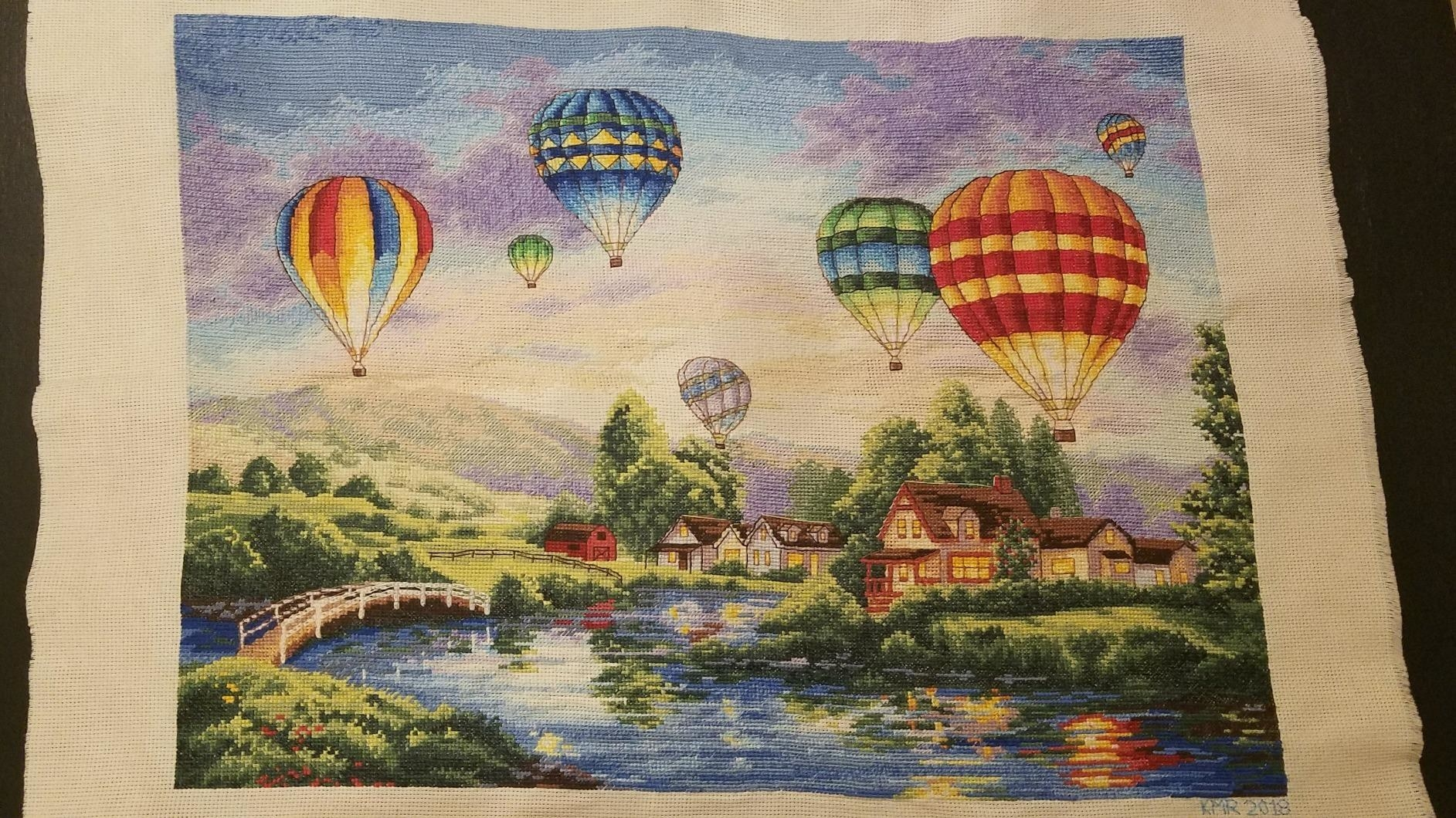 Reviewer photo of the completed cross stitch kit, which features a hot air balloons on a  picturesque background