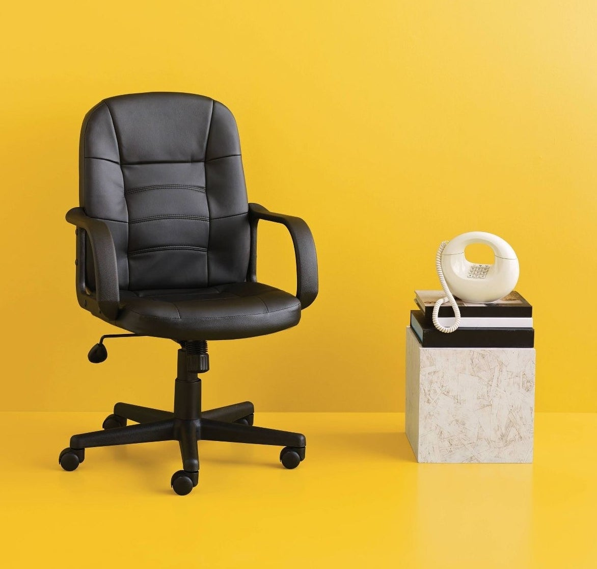 Black office chair with adjustable height next to marble table with an abstract white phone