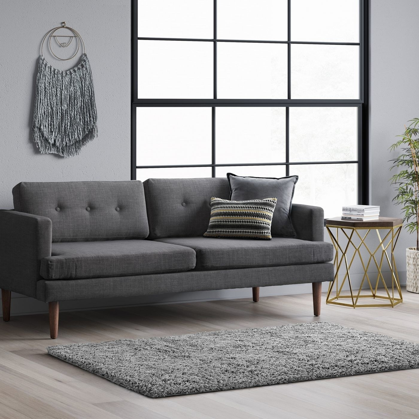 Plush gray shag rug on a hardwood floor below a gray couch with striped pillows