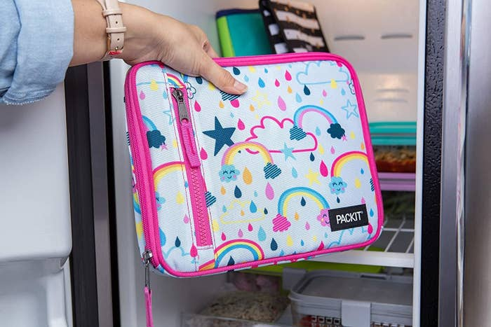 A model's hand placing a bright pink trimmed lunch bag with rainbow designs into a fridge