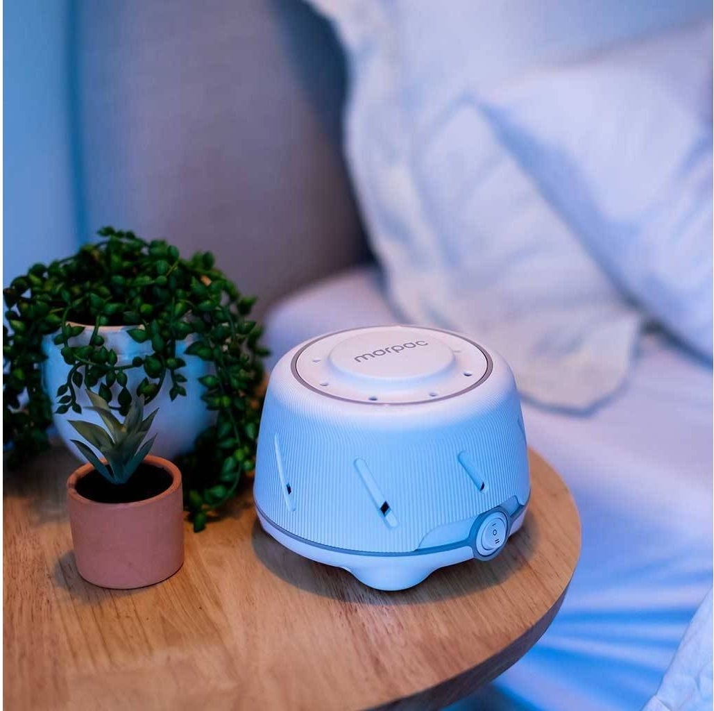 A white noise machine on a side table next to plant pots