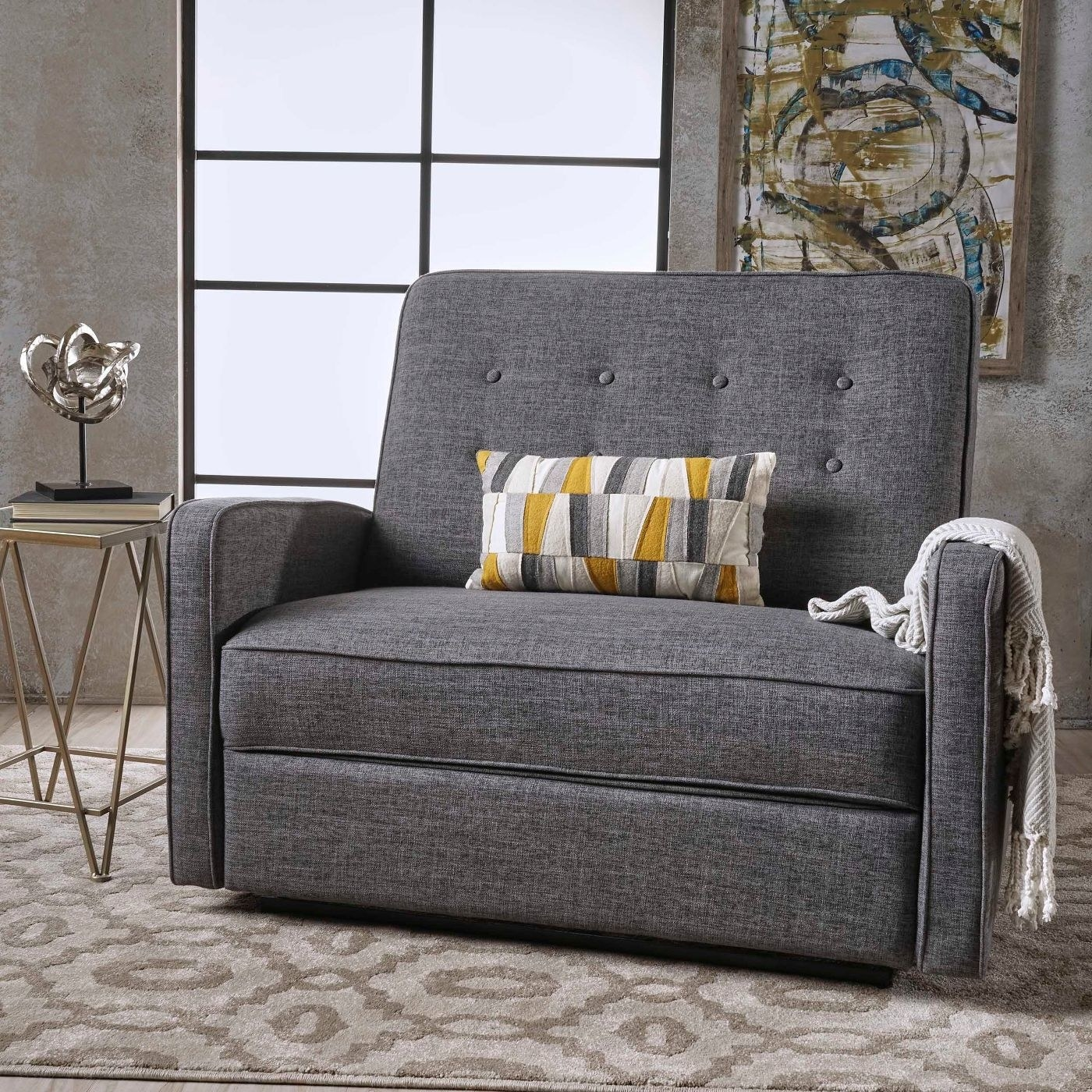 Gray reclining loveseat with a yellow and gray-patterned pillow and a white throw blanket