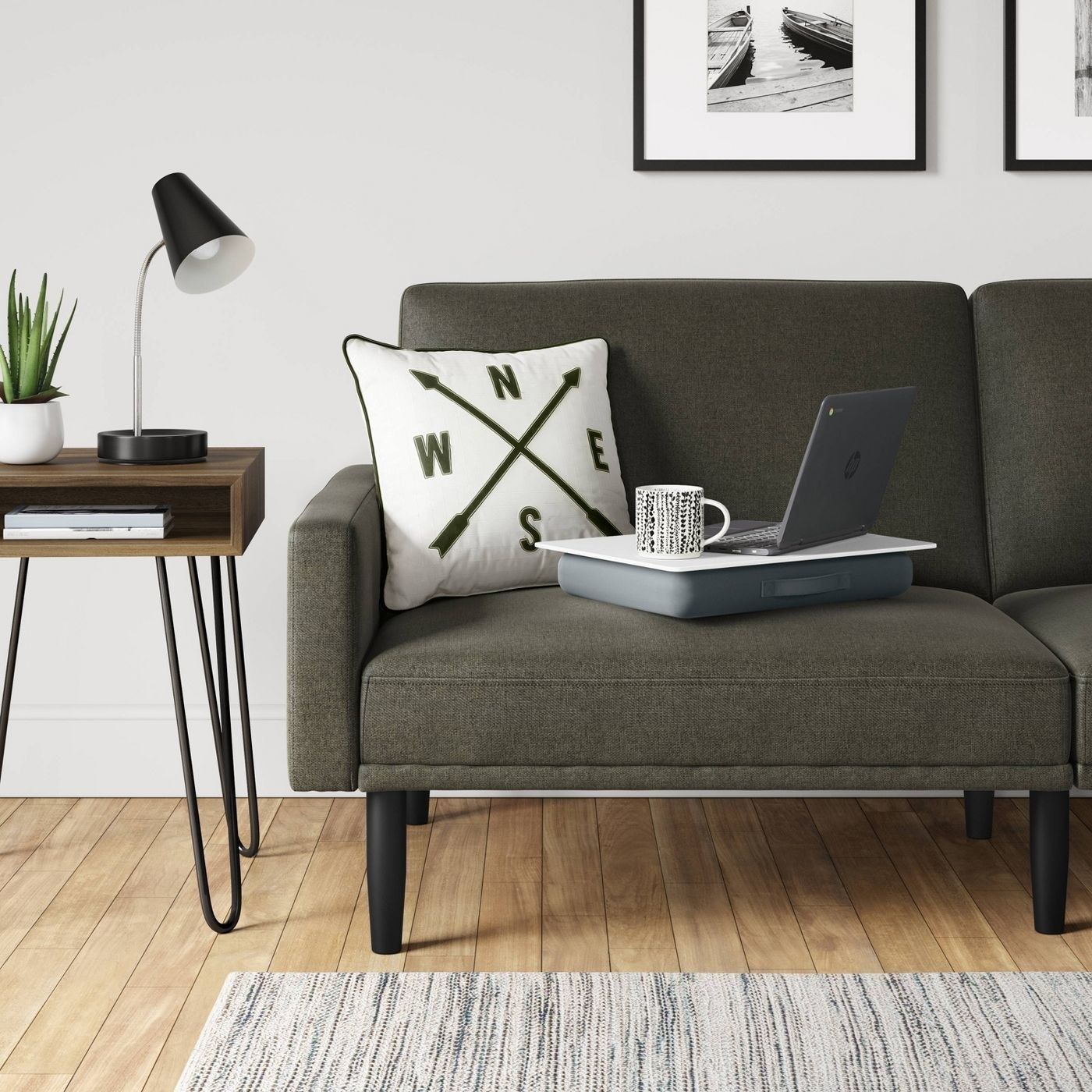 Gray lap desk on a dark gray couch with a compass pillow