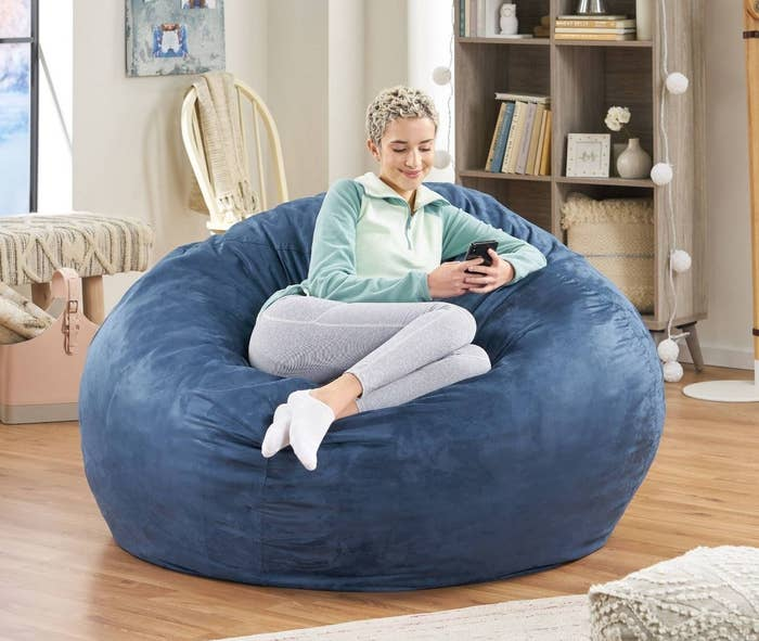 Model comfortably sits in dark blue bean bag while checking their cell phone