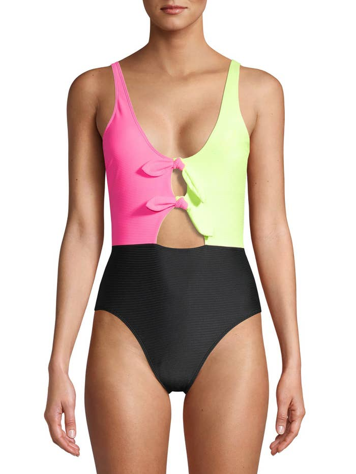 a model in a bathing suit where the top left is hot pink, the top right is neon yellow, and the bottom portion is black