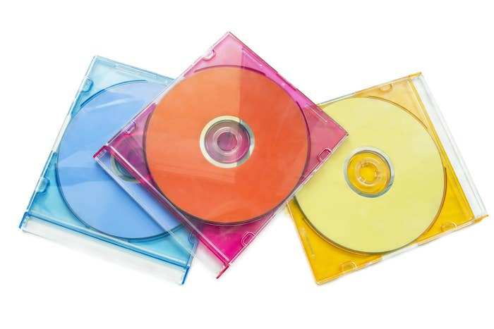 Three CD clear skinny jewel cases (one blue, hot pink, and yellow) with CDs inside them.