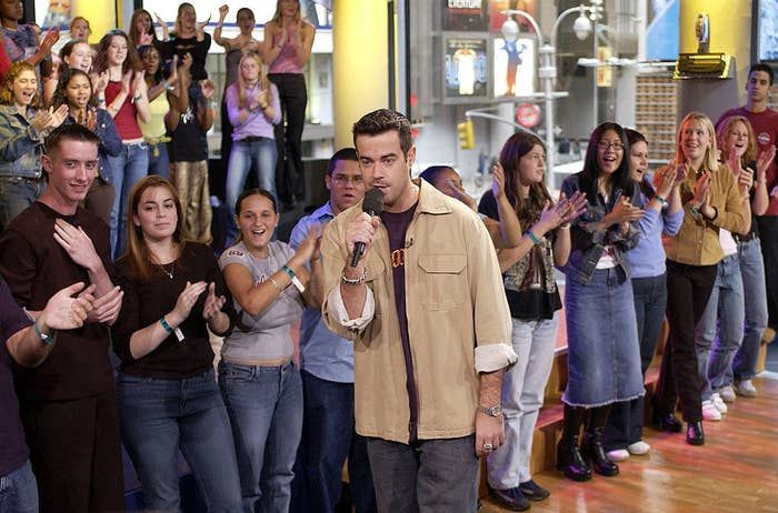 """Carson Daly on the set of """"TRL"""" with kids applauding behind him."""