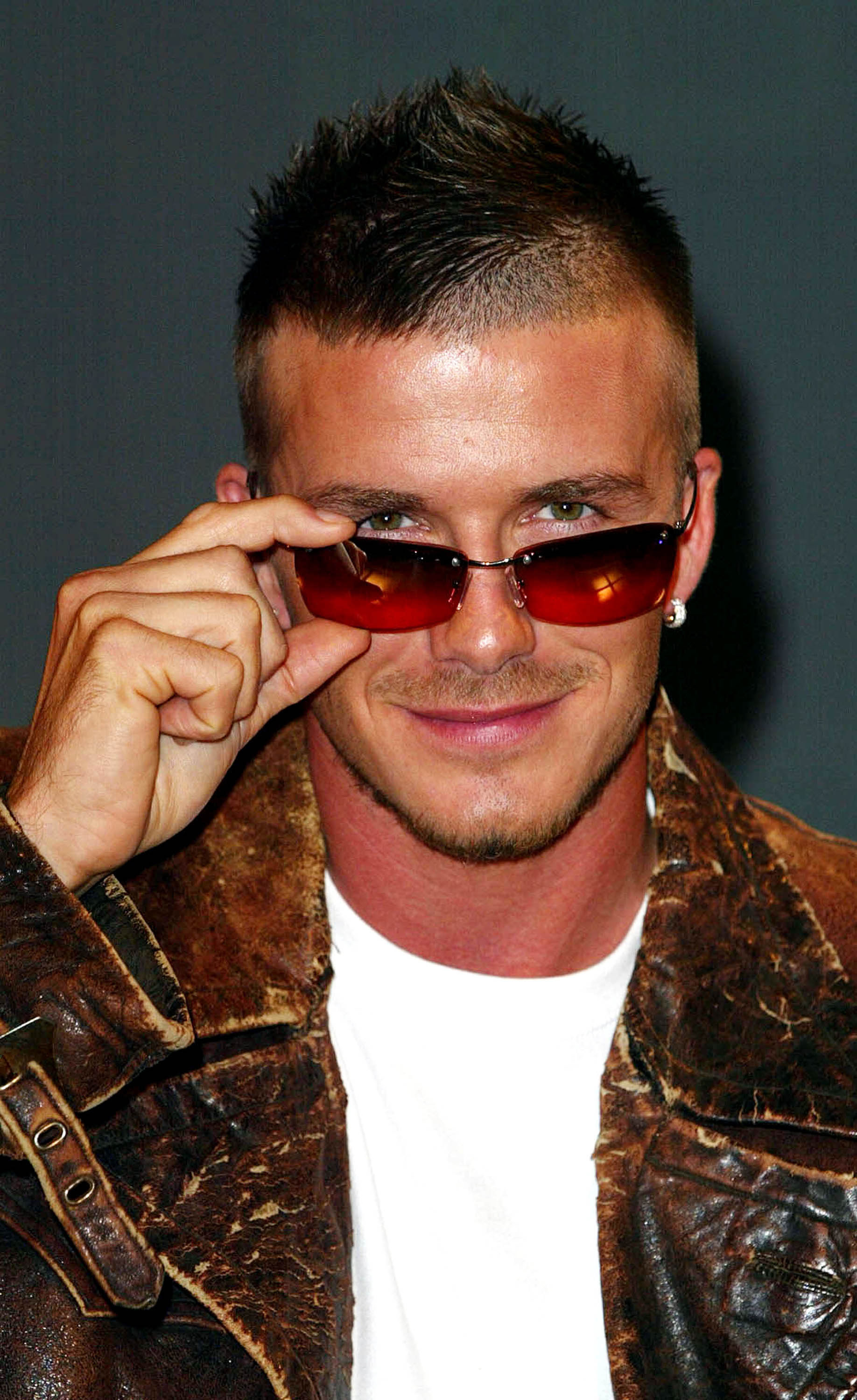 A photo of David Beckham slightly pulling down his brown-tinted sunglasses, while wearing a distressed brown leather jacket and white T-shirt.