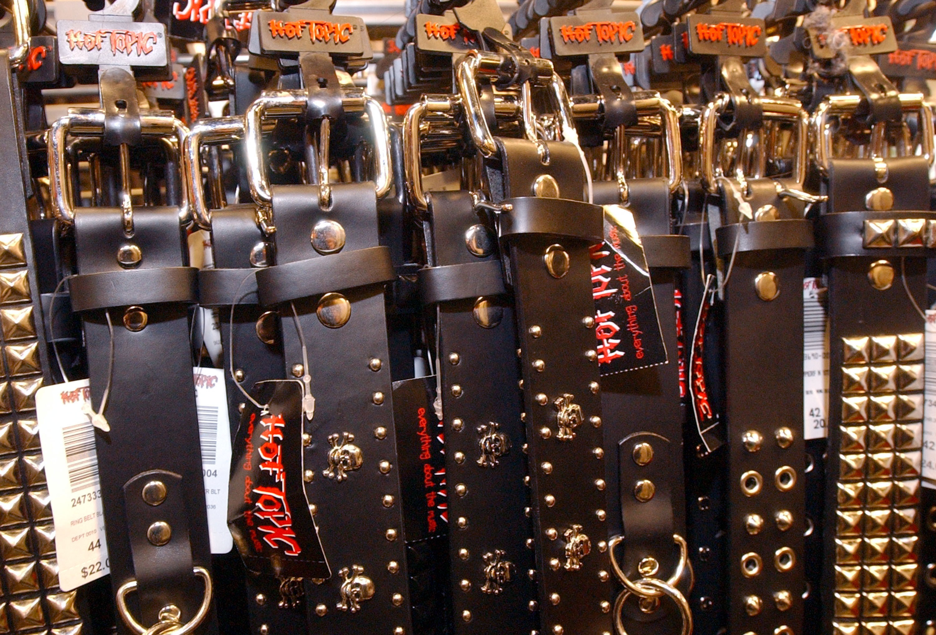 A close-up photo of a bunch of belts hanging on a rack in a Hot Topic.
