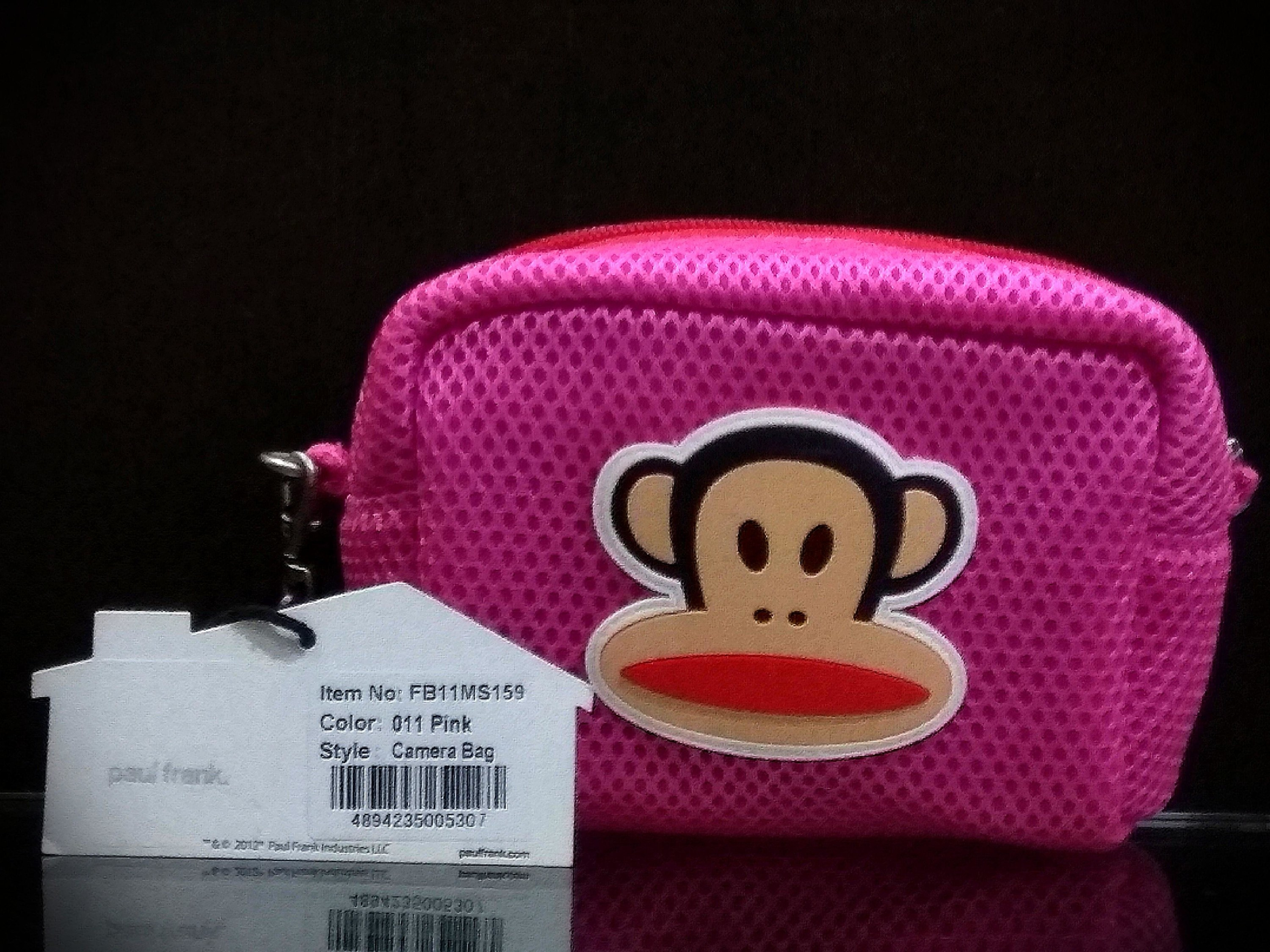 A hot pink Paul Frank camera case with the cartoon face of Julius the Monkey on it.