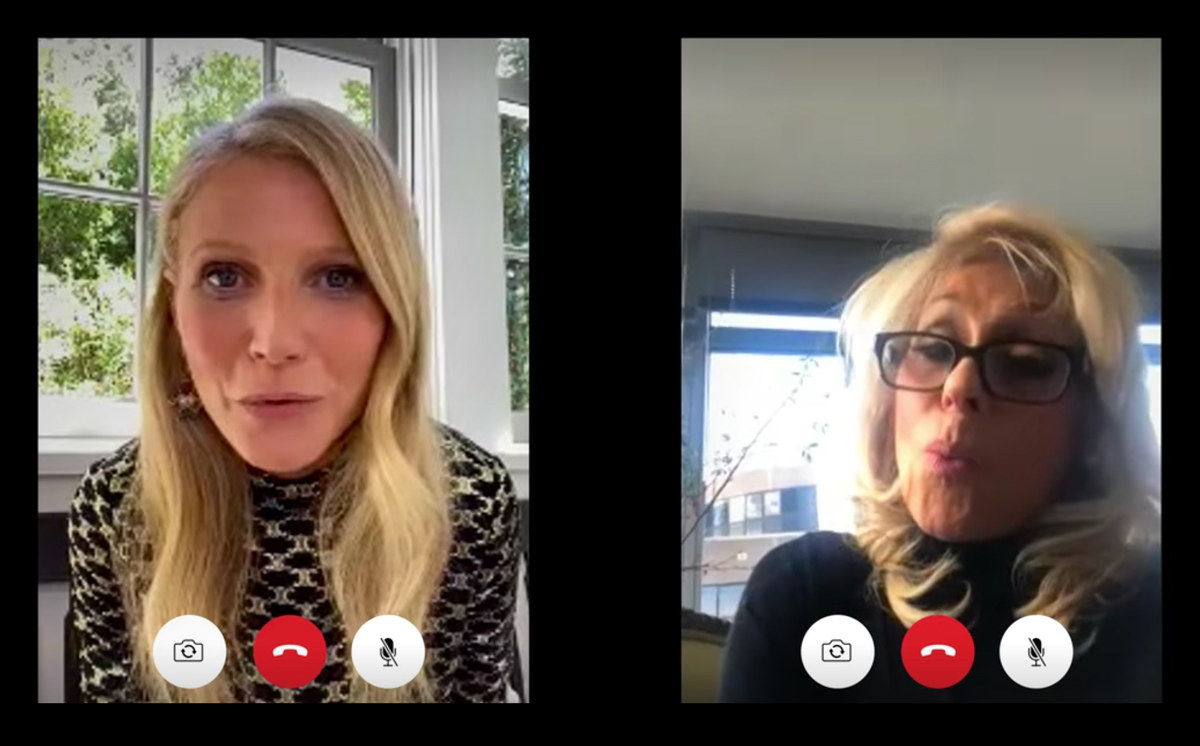 A still from The Politician showing Georgina and Dede both on Facetime talking to one another. Georgina wears a blue blouse and sits in front of a window while Dede wears glasses and a turtleneck. The phones show three icons for hang up, mute, and camera
