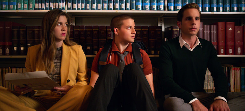 A image from The Politician showing Macafee, James, and Payton sitting on the floor against some bookshelves. Macafee wears a yellow blazer and James wears a red shirt, they both looking at payton in a black sweater looking nervous