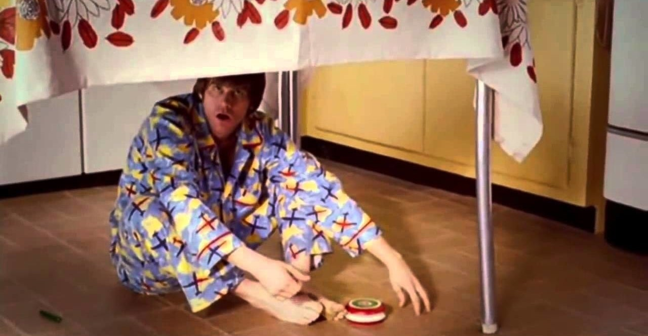 Grown up Joel in pajamas playing under a table.