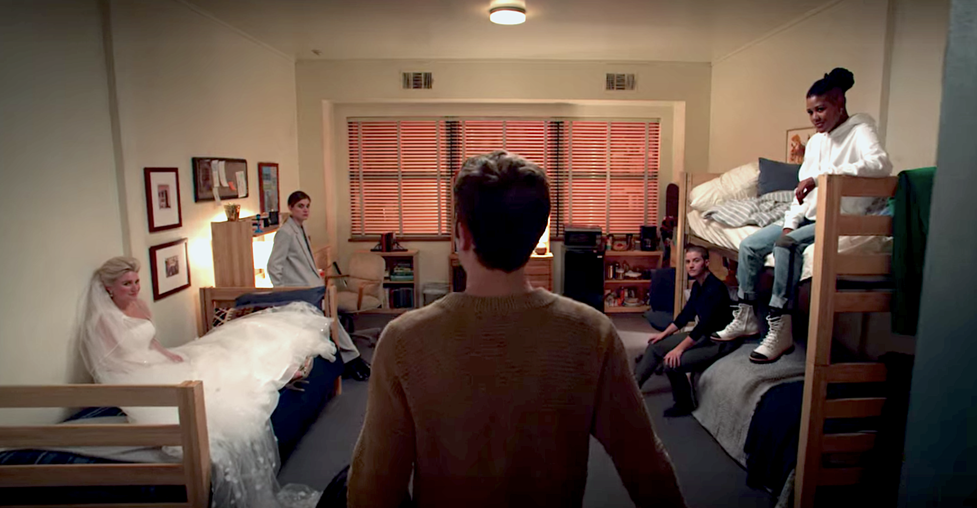 A still from The Politician showing Payton from behind walking into his dorm room and several characters sitting and waiting for him including Macafee, James, Sky, and Alice in a wedding dress