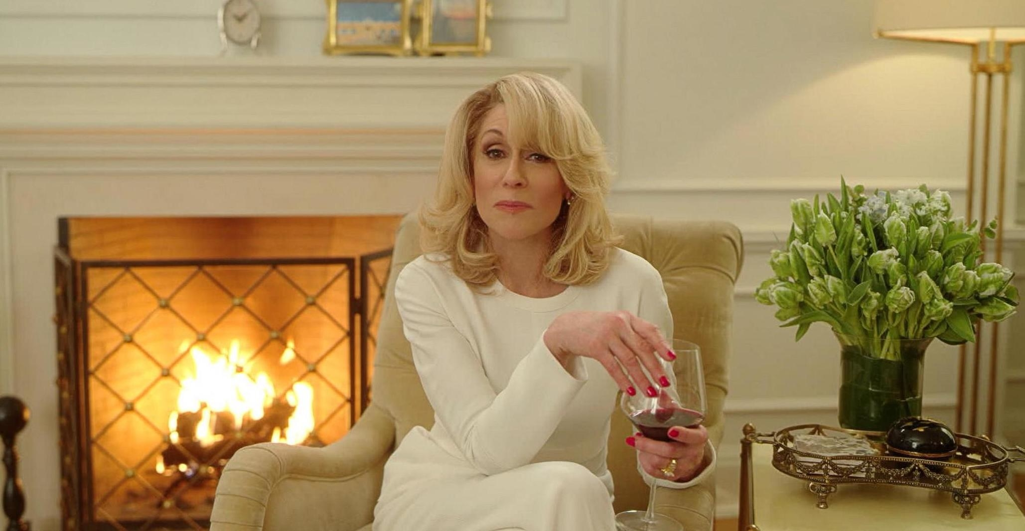 A still from The Politician showing Judith Light as Dede Standish sitting in a very white living room with a fire and a glass of wine looking into the camera. She wears a white dress and has perfectly blown out hair