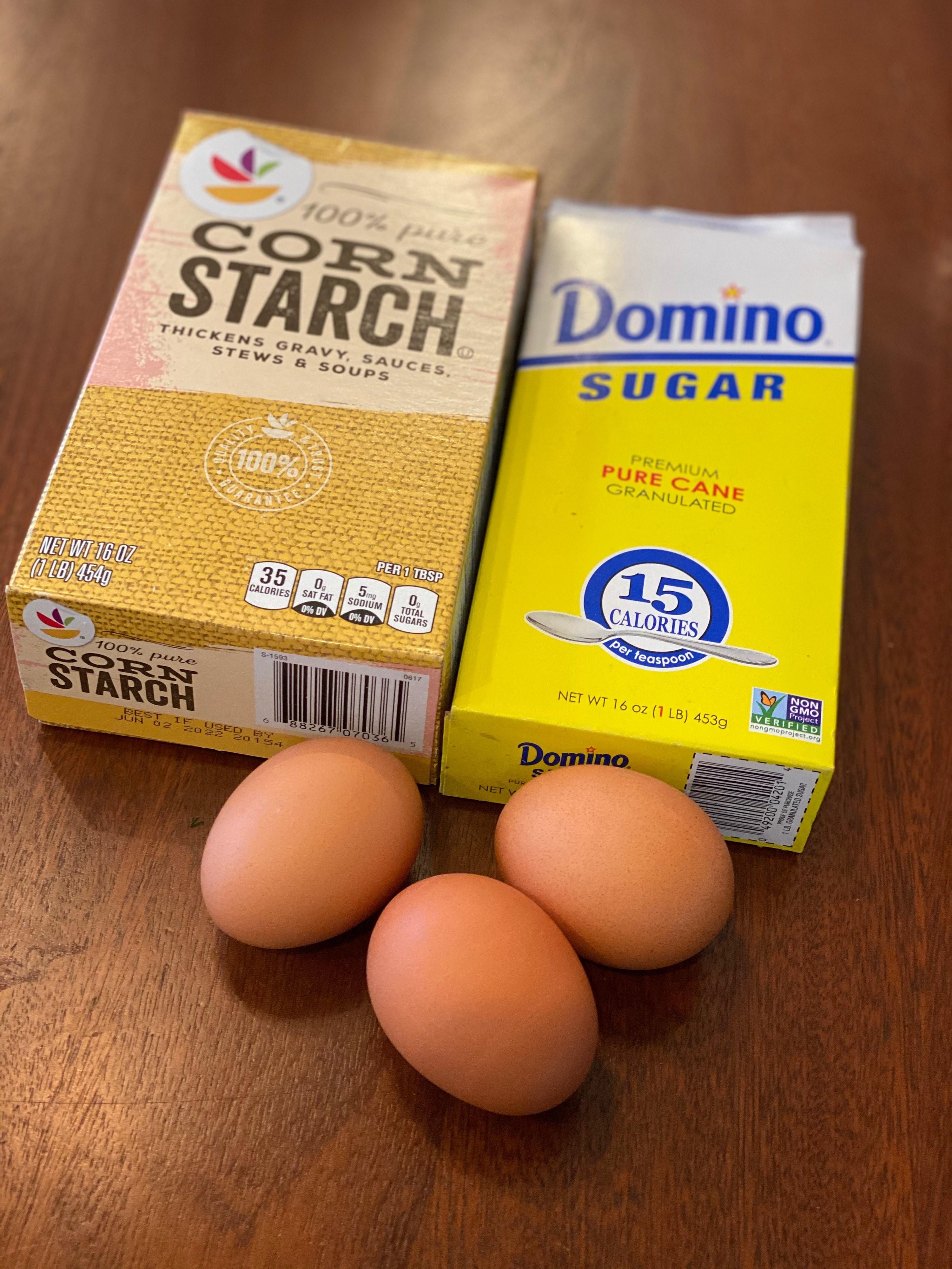 Three eggs, sugar, and cornstarch on a wooden countertop for cloud bread.
