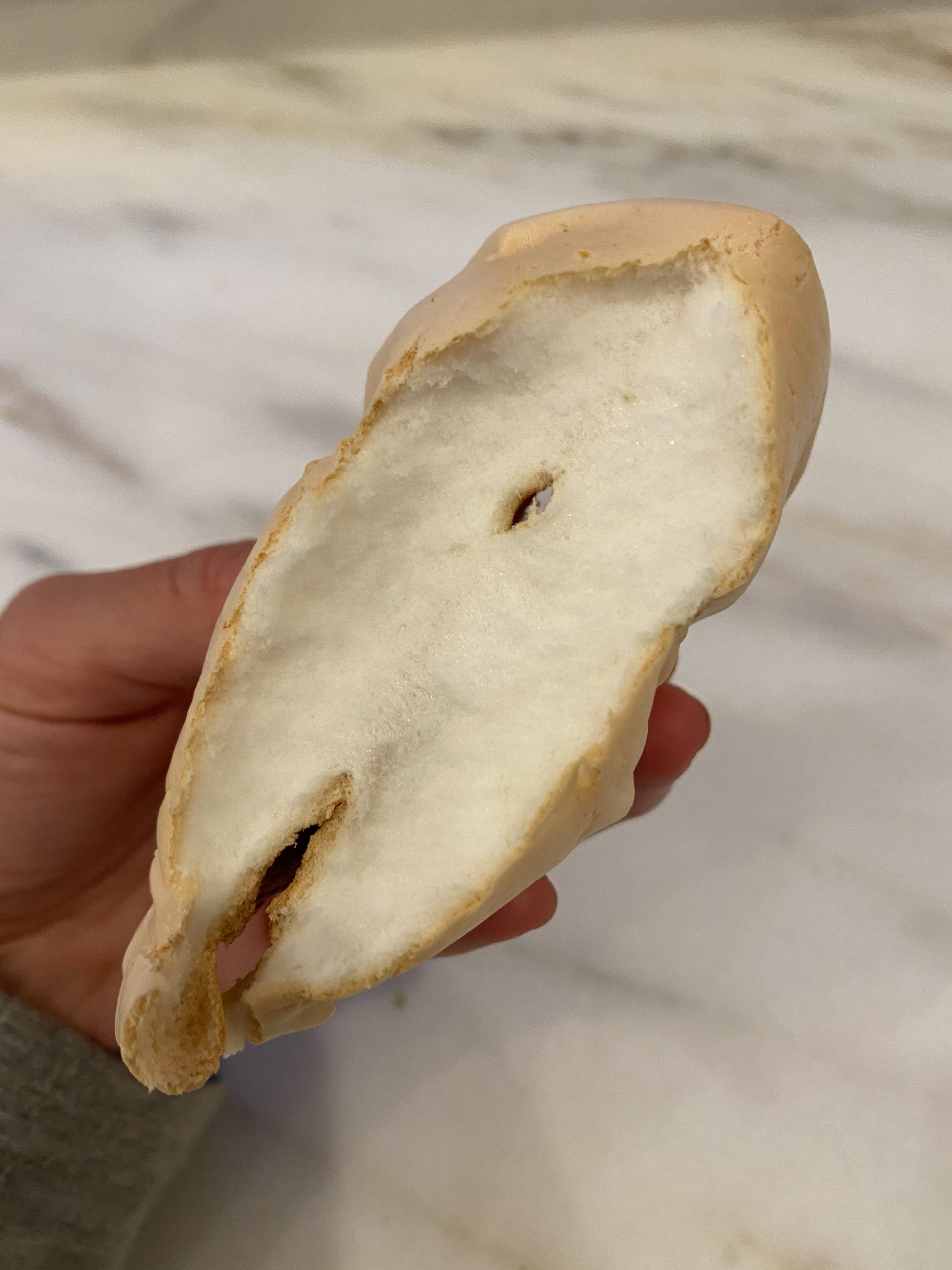 My hands holding a piece of cloud bread that is split in half, revealing a white and fluffy interior.
