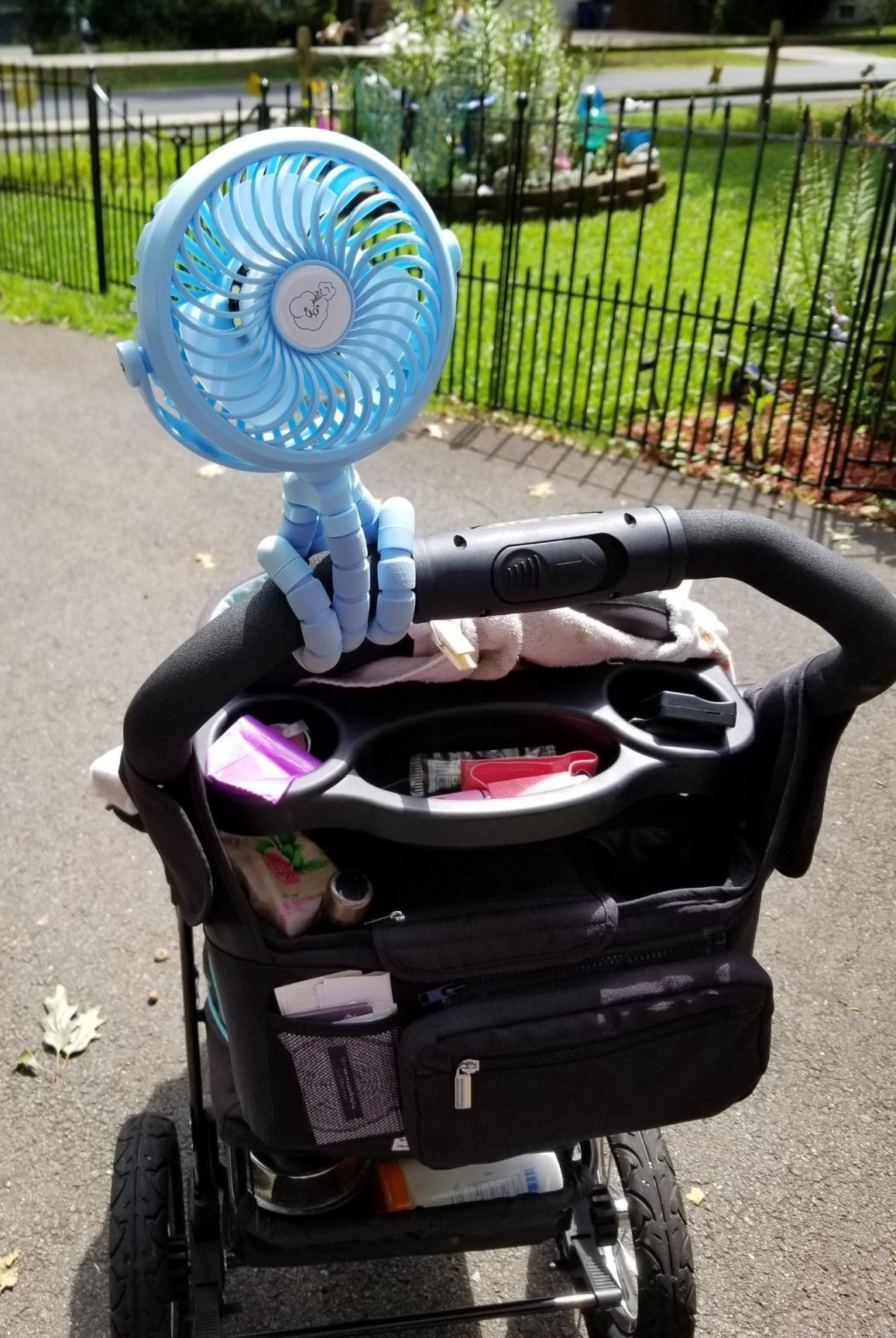 A reviewer's image of a light blue fan attached the handle of a stroller