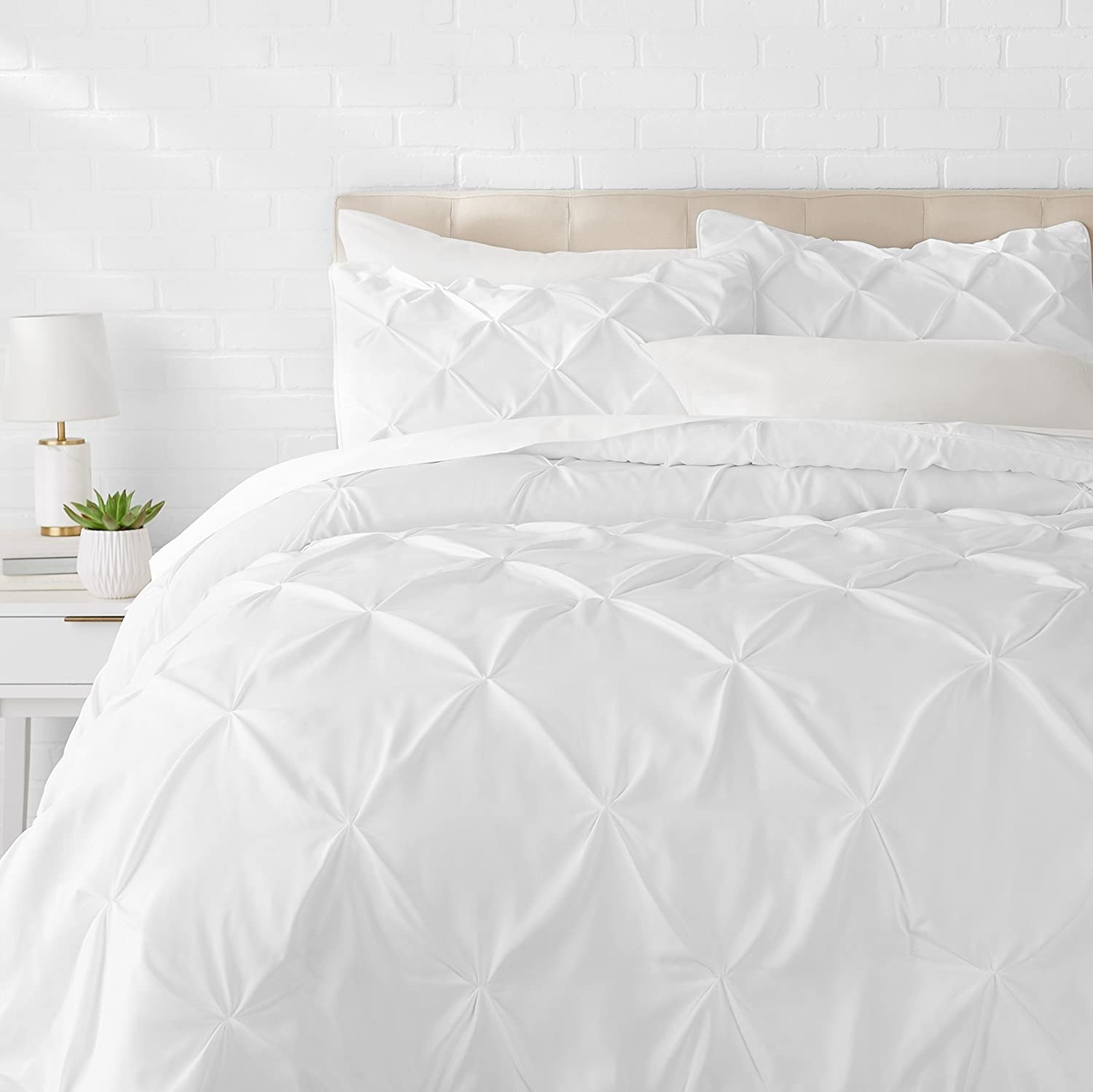 A bed with the pleated comforter and shams on it